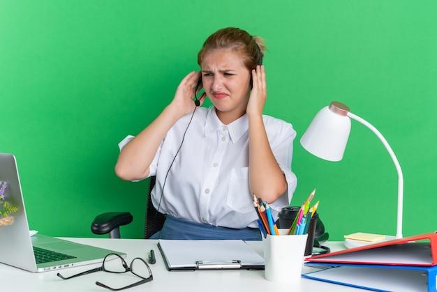 Stirnrunzelndes junges blondes callcenter-mädchen mit headset am schreibtisch sitzend mit arbeitswerkzeugen, die hände am headset halten und auf den laptop schauen