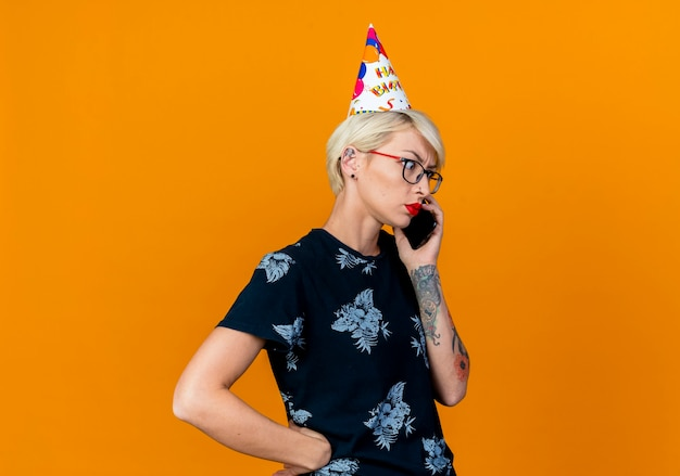 Stirnrunzelndes junges blondes partygirl, das brille und geburtstagskappe trägt, die am telefon spricht, das unten hand auf taille hält, die auf orange hintergrund mit kopienraum lokalisiert hält