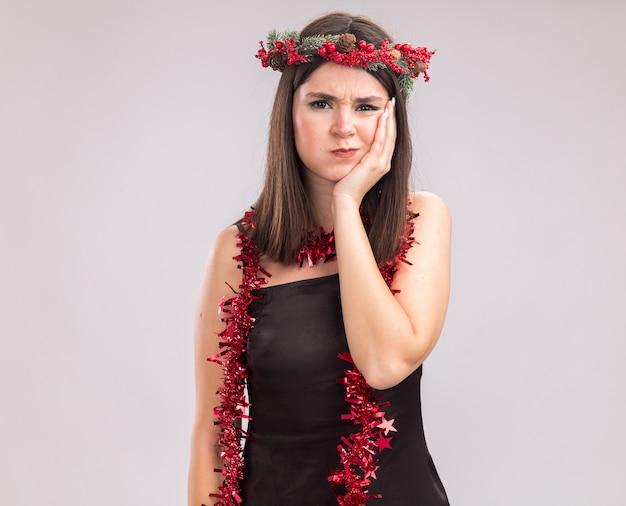 Stirnrunzelndes junges hübsches kaukasisches mädchen, das weihnachtskopfkranz und lametta-girlande um den hals trägt und in die kamera schaut, die die hand auf dem gesicht hält, mit aufgedunsenen wangen isoliert auf weißem hintergrund mit kopierraum