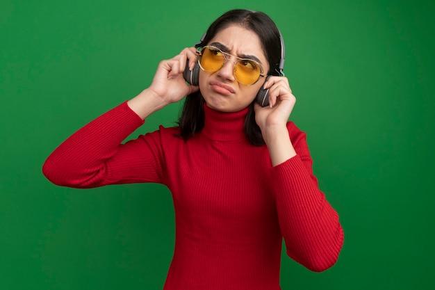 Stirnrunzelndes junges hübsches kaukasisches mädchen mit sonnenbrille und kopfhörern, das kopfhörer mit blick auf die seite greift