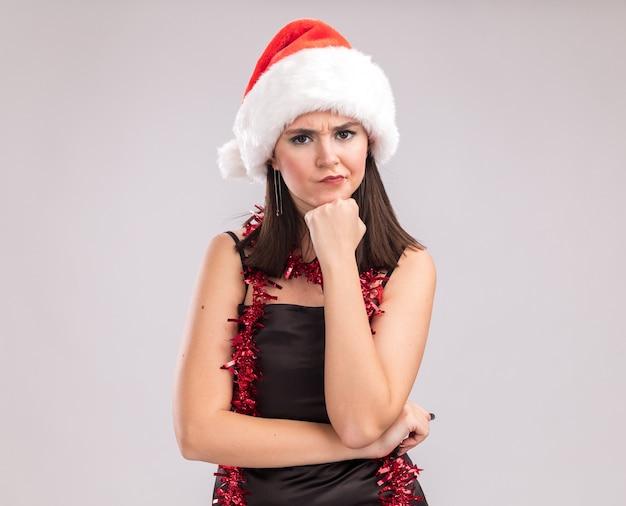 Stirnrunzelndes junges hübsches kaukasisches mädchen mit weihnachtsmütze und lametta-girlande um den hals, das in die kamera schaut und die hand am kinn hält, isoliert auf weißem hintergrund mit kopierraum