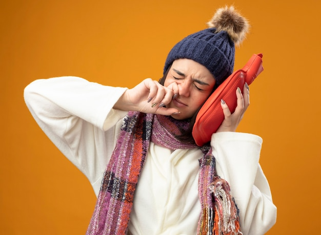 Stirnrunzelndes junges kaukasisches krankes mädchen, das robe wintermütze und schal berührt kopf mit heißem wasserbeutel abwischend nase mit geschlossenen augen lokalisiert auf orange wand