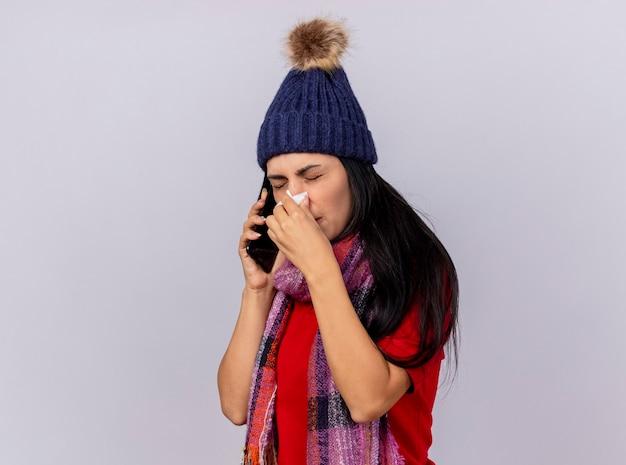 Stirnrunzelndes junges kaukasisches krankes mädchen, das wintermütze und schal trägt, die in der profilansicht stehen und am telefon sprechen, das nase mit serviette abwischt, lokalisiert auf weißem hintergrund mit kopienraum