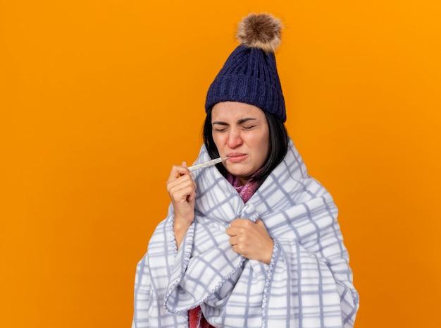 Stirnrunzelndes junges kaukasisches krankes mädchen, das wintermütze und schal wickelt, die in das plaid halten, das thermometer im mund hält, das plaid mit geschlossenen augen, die auf orangefarbenem hintergrund mit kopienraum isoliert sind, ergreift
