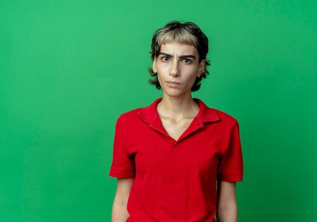 Stirnrunzelndes junges kaukasisches mädchen mit pixie-haarschnitt stehend und betrachten kamera lokalisiert auf grünem hintergrund mit kopienraum