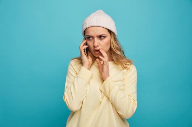 Stirnrunzelndes junges mädchen, das wintermütze trägt, die am telefon spricht und hand in der nähe des mundes flüstert und seite betrachtet