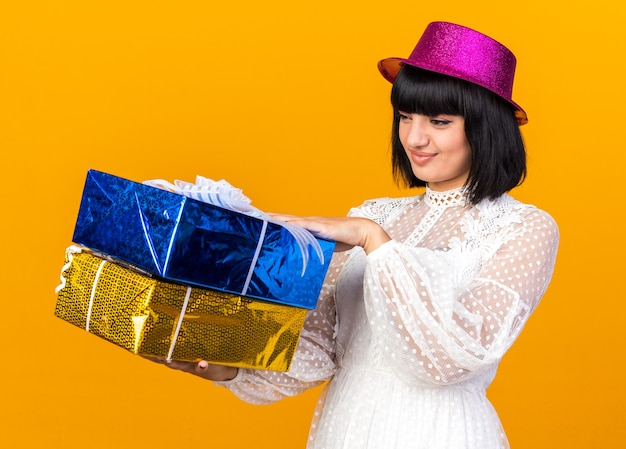 Stirnrunzelndes junges partymädchen mit partyhut, das in der profilansicht steht und geschenkpakete isoliert auf orangefarbener wand hält und betrachtet