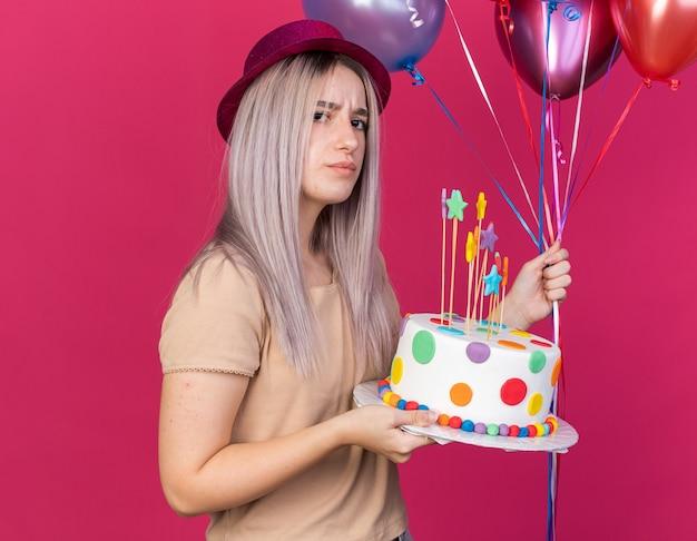 Stirnrunzelndes junges schönes mädchen mit partyhut, das luftballons mit kuchen hält, isoliert auf rosa wand