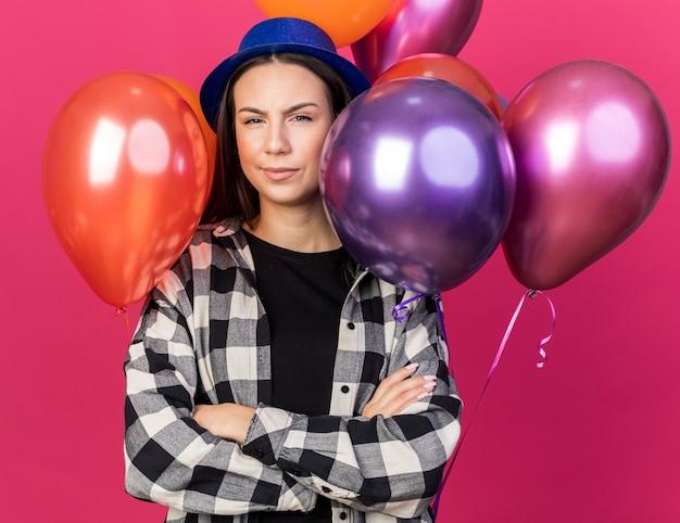 Stirnrunzelndes junges schönes mädchen mit partyhut, das vor ballons steht, die die hände kreuzt