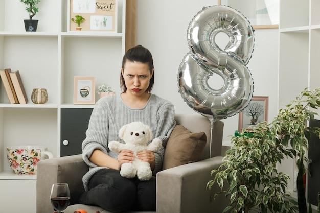 Stirnrunzelndes schönes mädchen am glücklichen frauentag mit teddybär, der auf einem sessel im wohnzimmer sitzt