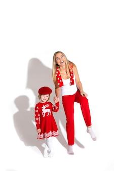 Stock foto der fröhlichen blonden mutter in der roten hose, im weißen oberteil und im roten schal, die tochterhand halten. tochter trägt rotes winterkleid und baskenmütze. studioaufnahme.