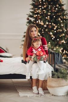 Stock foto der liebenden mutter im grünen kleid, das ihrer kleinen tochter im pyjamakleid ein weihnachtsgeschenk gibt. sie stehen neben einem wunderschön geschmückten weihnachtsbaum unter schneefall.
