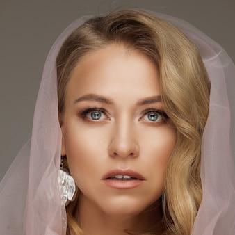 Stock foto einer wunderschönen blonden frau mit blauen augen und natürlichem make-up, die einen rosa schleier trägt und eine zerbrechliche rosa rose hält. braut-konzept.