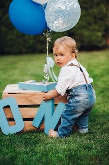 Stock foto eines entzückenden kleinen jungen in jeans, hemd und hosenträgern, der mit geburtstagsdekorationen auf dem rasen im hinterhof spielt. sommertag aus. geburtstag konzept. luftballons und holzbuchstaben.