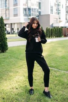 Stock foto eines hübschen sportlichen mädchens in schwarzem pullover und joggern, die eine kapuze aufsetzen, während sie eine kaffeetasse zum mitnehmen halten. stilvolles mädchen in schwarzer sportlicher kleidung und turnschuhen, die auf grünem rasen stehen.