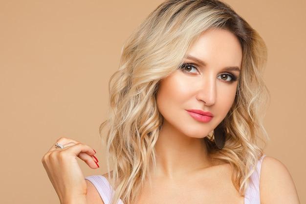 Stock foto headshot einer hübschen blonden frau mit welligem haar und rosa lippen und smokey eyes blick in die kamera. sie hat rote nägel. auf beigem hintergrund isolieren. studioportrait.