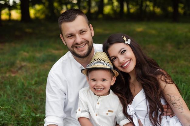 Stock foto kopfschuss einer schönen kaukasischen familie von mutter, vater und ihrem sohn, die glücklich an der kamera im park am sommertag lächeln.