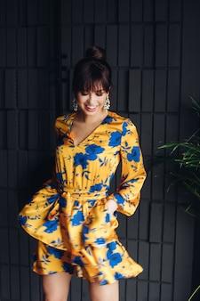 Stock foto porträt einer wunderschönen brünette in schönen gelben und blauen insgesamt oder anzug bewegen und lächelnd nach unten. modeporträt.