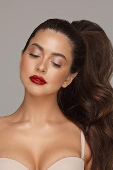 Stock foto porträt eines schönen jungen mädchens mit perfektem make-up und roten lippen. sie hat wunderschönes, dickes haar, das bis zum schwanz hochgesteckt ist. nach unten schauend, bh tragend. studioaufnahme.