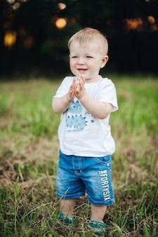 Stock foto porträt in t-shirt und jeans-shorts hände klatschen und lächelnd stehend auf grünem rasen im park. bokeh-hintergrund. fröhliches baby, das mit klatschenden händen auf gras steht.