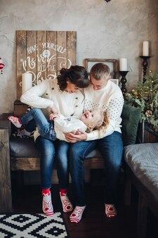 Stock foto porträt von glücklichen eltern in weißen pullovern kitzeln ihre kleine tochter auf den knien. tochter lacht fröhlich. weihnachtsdekorationen.