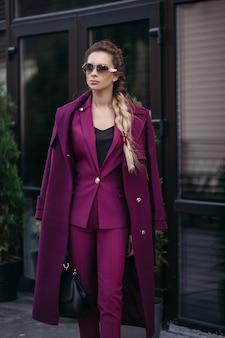 Stock foto portrait von stilvollen geschäftsfrau mit zopf sonnenbrille, modischen hellvioletten anzug und trenchcoat über ihre schultern tragen. in der hand hält sie eine luxuriöse ledertasche.