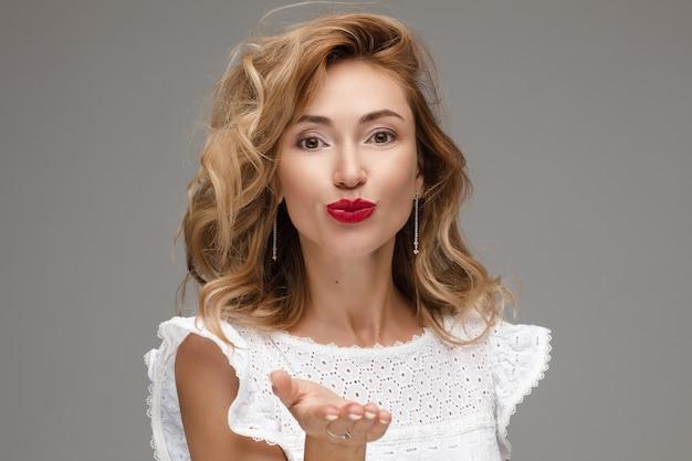 Stock foto studio portrait eines wunderschönen jungen erwachsenen kaukasischen modells mit unordentlichen blonden haaren und roten lippen in romantische weiße bluse luftkuss an die kamera senden. auf grau isolieren.