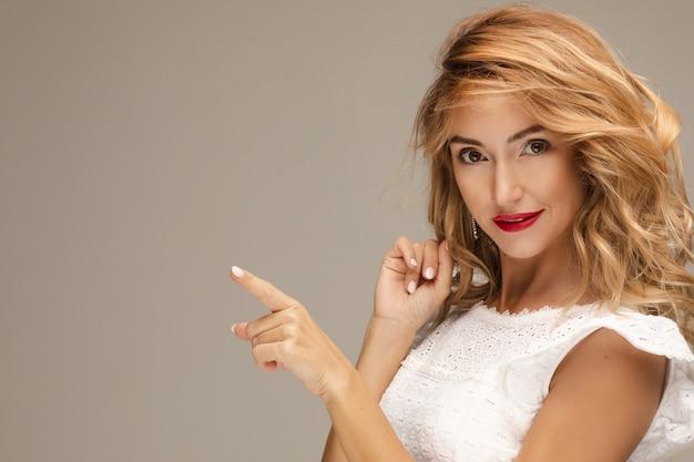 Stock foto studioportrait einer attraktiven jungen frau mit blonden haaren und roten lippen in weißer bluse, die auf textfreiraum zeigt. rote lippen. isolieren. studio. blick in die kamera.