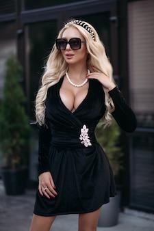 Stock foto von atemberaubender schlanker frau mit dekolleté in schwarzem kleid und sonnenbrille, die im freien posiert. sexy model mit langen blonden haaren posiert im schwarzen kleid auf der straße.