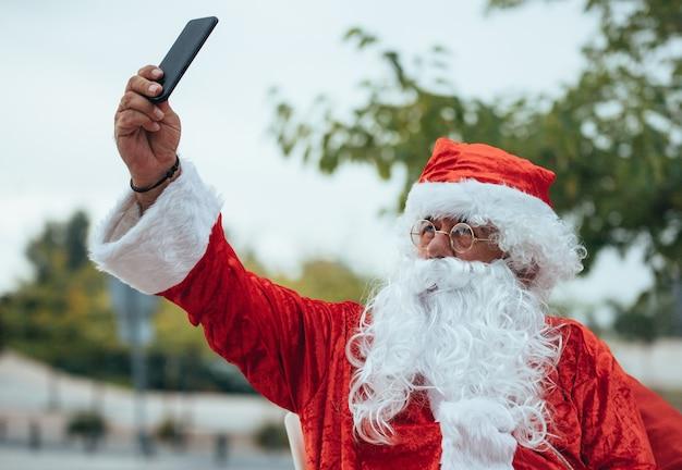 Stock foto von santa claus, der ein selfie mit dem handy in der einen hand und in der anderen macht