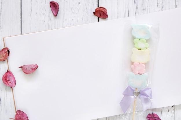 Stock fotografie flach legen vintage weiß lackiert holz tisch notizbuch papier blütenblätter zuckerwatte