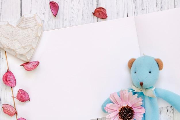 Stock fotografie flach legen vintage weiß lackiert holztisch lila blütenblätter tragen puppe herz handwerk