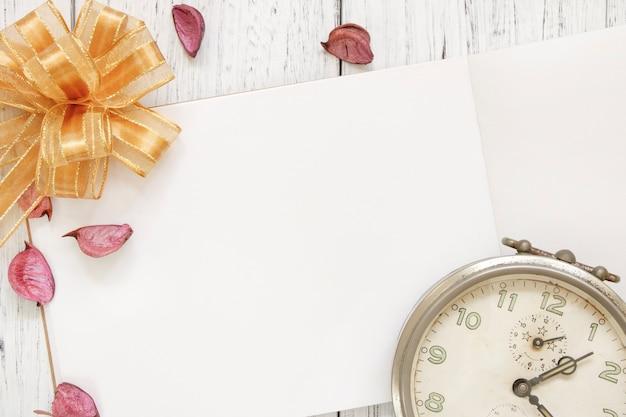 Stock fotografie flach legen vintage weiß lackiert holztisch lila blütenblätter vintage wecker goldenes band