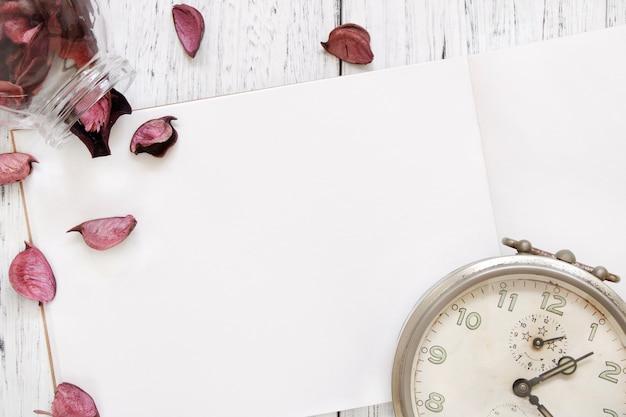 Stock fotografie flach legen vintage weiß lackiert holztisch lila blütenblätter vintage wecker