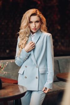 Stock portrait einer atemberaubenden eleganten frau mit langen, gewellten blonden haaren, die hellblauen business-anzug mit hose trägt. sie schaut genau in die kamera. geschäftsdame im anzug im café.