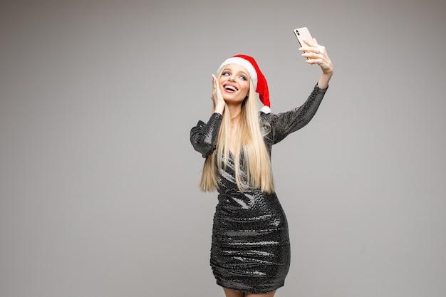 Stockfoto der attraktiven blonden kaukasischen frau in der weihnachtsmannmütze und im funkelnden kleid