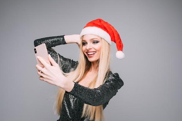 Stockfoto der attraktiven kaukasischen frau in der roten weihnachtsmütze und im grauen glänzenden kleid, das selfie über smartphone macht