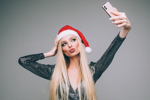 Stockfoto der herrlichen blonden frau in der roten weihnachtsmütze und im funkelnden kleid, die selbstporträt über smartphone machen