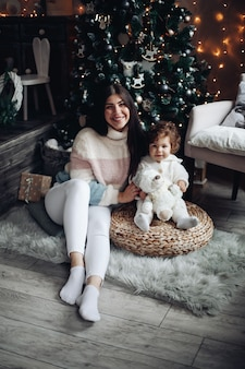 Stockfoto der lächelnden attraktiven mutter und des babys, die zu hause unter geschmücktem weihnachtsbaum sitzen.