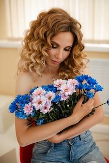 Stockfoto der oben ohne sinnlichen schönen frau mit hellem welligem haar, das bündel der rosa und blauen chrysanthemenblumen umarmt.