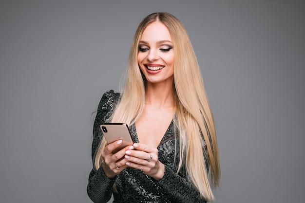 Stockfoto des attraktiven blonden mädchens im funkelnden cocktailkleid unter verwendung des handys, um mit freunden zu chatten