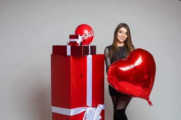 Stockfoto des brünetten mädchens im schwarzen kleid, das roten herzförmigen ballon hält, der neben eingewickelten geschenken steht. luftballon mit verkaufswort oben auf geschenken.