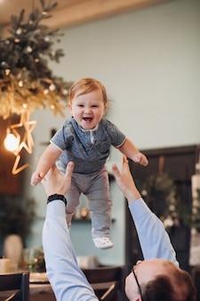 Stockfoto des gemütlichen kleinen jungen in der luft, während vater mit ihm zu hause spielt. vater warf seinen sohn in die luft und fing ihn auf. baby lacht. weihnachtsschmuck im hintergrund.