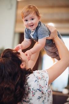 Stockfoto des glücklichen lachenden kindes, das mit seiner mutter spielt. brünette mutter hält ihren sohn in die luft. glück. familienkonzept.