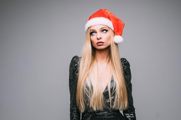 Stockfoto des unglücklichen mädchens mit langen blonden haaren, die weihnachtsmannmütze und schwarzen funkelnden hut tragen