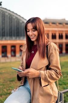 Stockfoto einer jungen kaukasischen frau, die ihr smartphone benutzt und lächelt. sie schreibt eine sms.