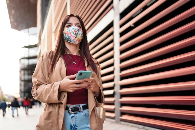 Stockfoto einer jungen kaukasischen frau, die ihr smartphone in der straße benutzt. sie trägt eine gesichtsmaske wegen covid19.