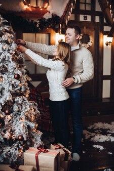 Stockfoto eines lächelnden romantischen paares, das weihnachtsbaum zusammen verziert
