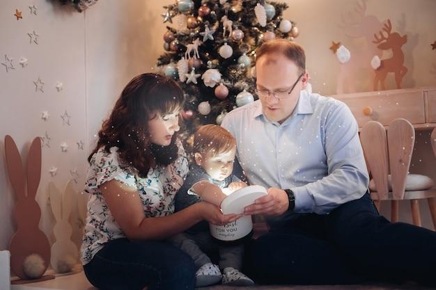 Stockfoto porträt der glücklichen kaukasischen familie, die die box mit weihnachtsgeschenk in box öffnet. sie sitzen am geschmückten weihnachtsbaum im kinderzimmer.