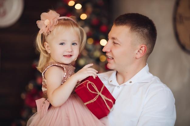 Stockfoto porträt des attraktiven jungen erwachsenen vaters mit der kleinen blonden tochter mit eingewickelten weihnachtsgeschenken.